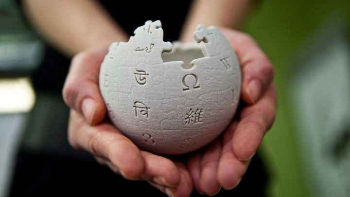 Hände halten Wikipedia-Puzzleball