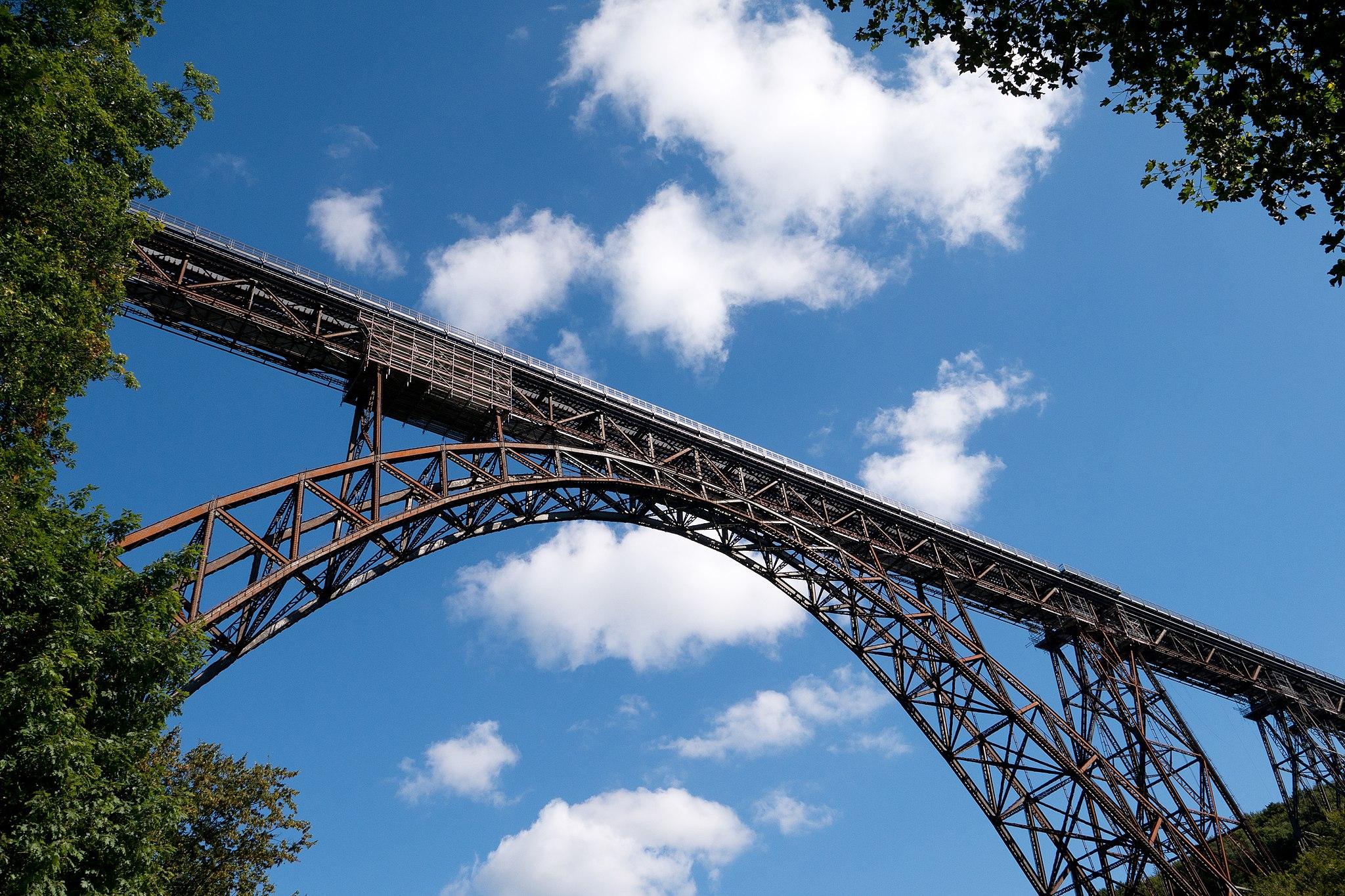 Die Müngstener Brücke, fotografiert von unten mit Blick auf einen blauen Himmel an einem sonnigen Tag.